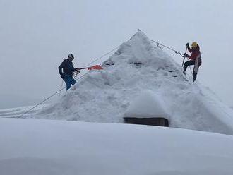 Sneh zo striech zhadzujú horolezci
